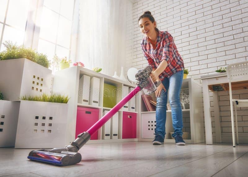 Η γυναίκα σκουπίζει το πάτωμα με ηλεκτρική σκούπα στοκ φωτογραφία με δικαίωμα ελεύθερης χρήσης