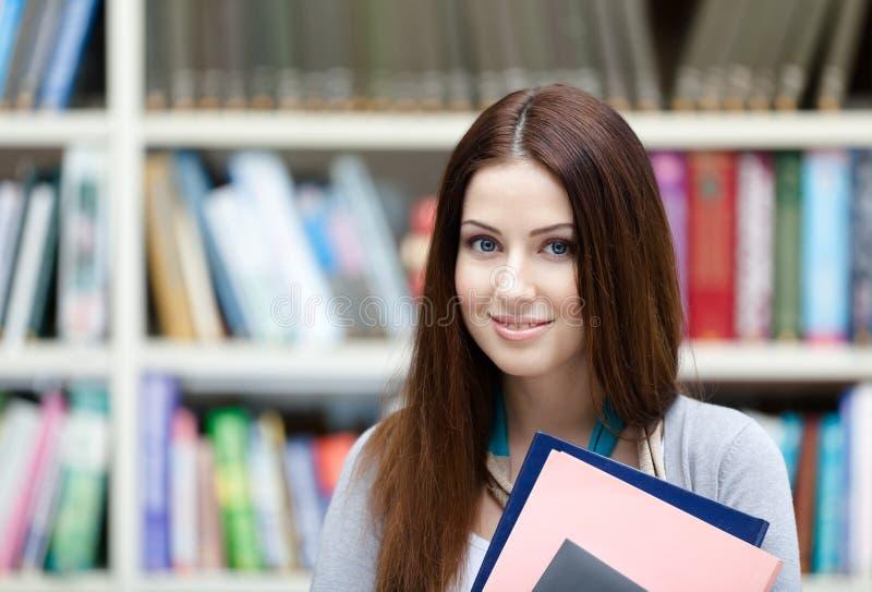 Η γυναίκα σπουδαστής κρατά τα βιβλία στοκ εικόνα