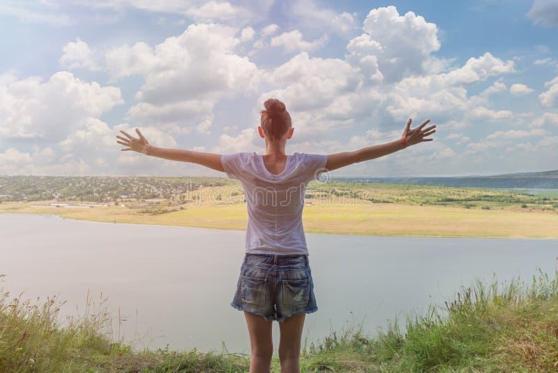 Η γυναίκα στέκεται πίσω με τις ανοικτές αγκάλες Η άποψη του ποταμού και του λόφου μπλε ουρανός σύννεφων glare στοκ εικόνα