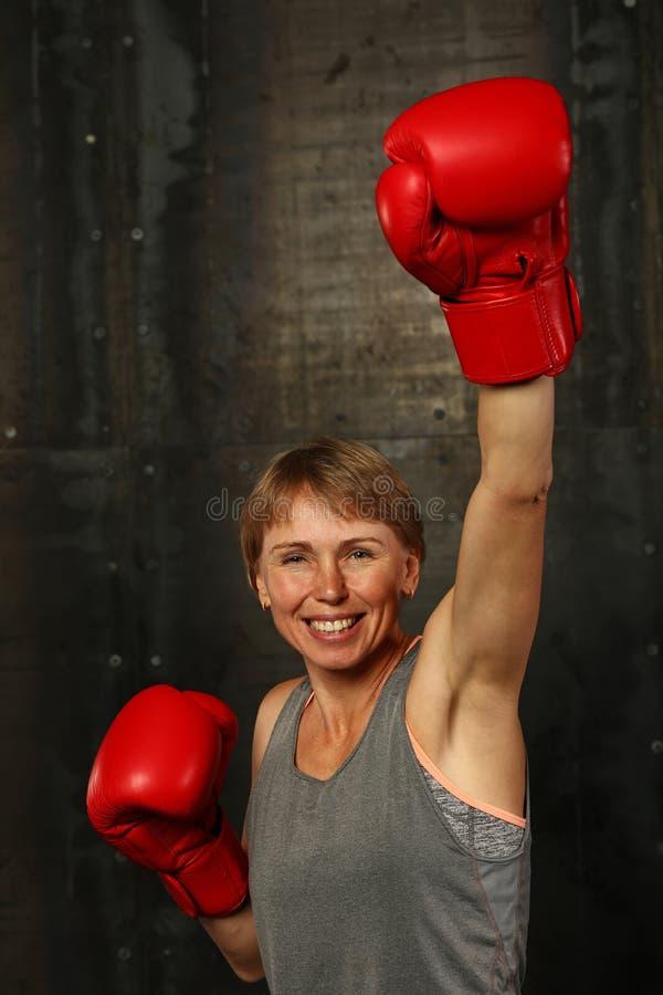 Η γυναίκα στα εγκιβωτίζοντας γάντια με το χέρι κερδίζει επάνω τη χειρονομία στοκ εικόνα