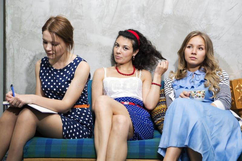 Η γυναίκα στα διαφορετικά φορέματα κάθεται στον καναπέ στοκ εικόνες