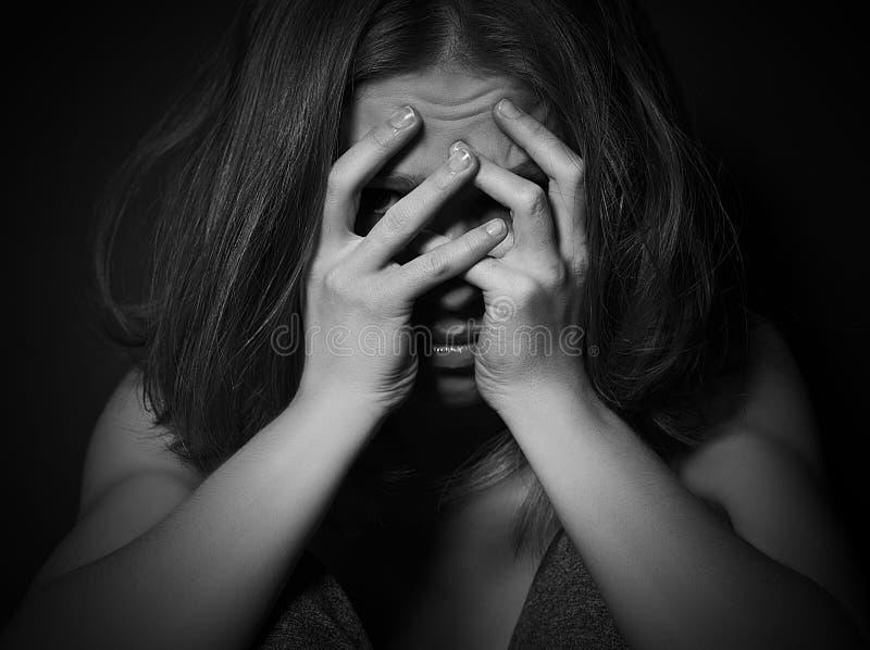 Η γυναίκα στην κατάθλιψη και την απελπισία που φωνάζουν, κάλυψε το πρόσωπό της στο bla στοκ φωτογραφίες