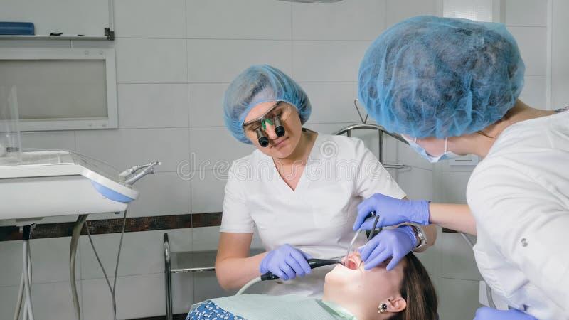 Η γυναίκα στην κλινική οδοντιάτρων παίρνει την οδοντική επεξεργασία για να γεμίσει μια κοιλότητα σε ένα δόντι Οδοντική αποκατάστα στοκ φωτογραφίες