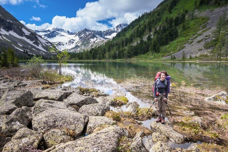 Η γυναίκα στο ίχνος στη λίμνη στα βουνά Altai στοκ εικόνες