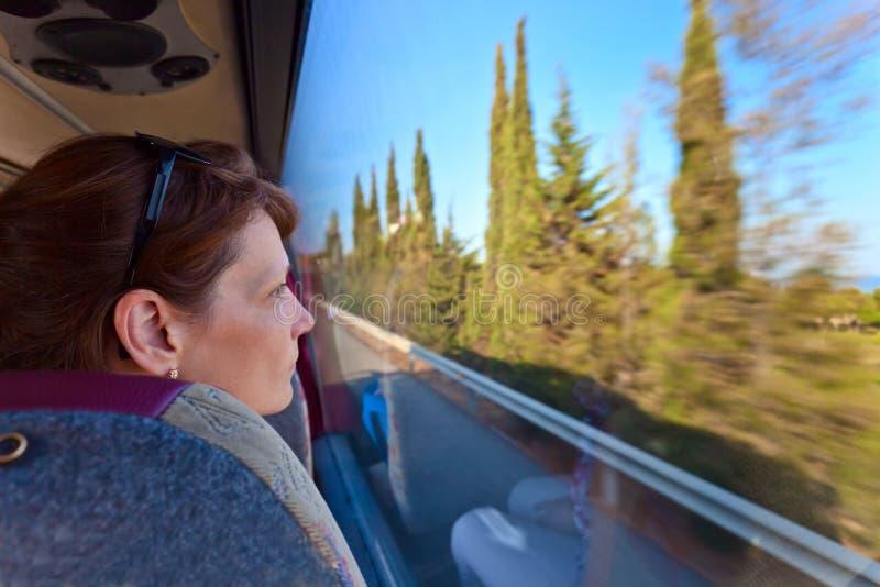 Η γυναίκα στο λεωφορείο κοιτάζει από το παράθυρο στοκ εικόνα