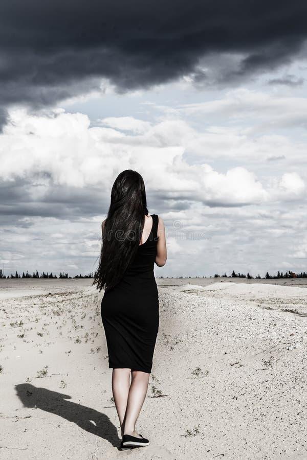 Η γυναίκα στο Μαύρο ντύνει σε μια έρημο στοκ εικόνα