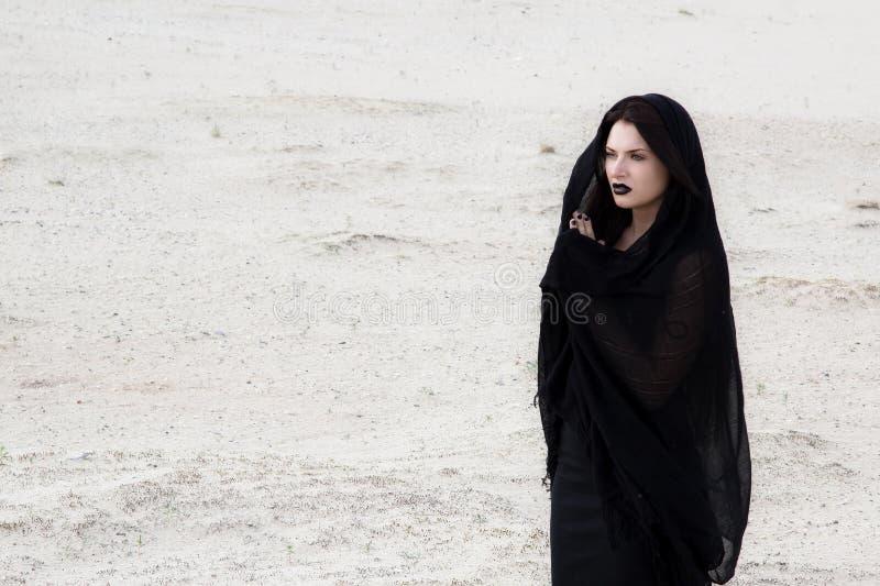 Η γυναίκα στο Μαύρο ντύνει σε μια έρημο στοκ φωτογραφία με δικαίωμα ελεύθερης χρήσης