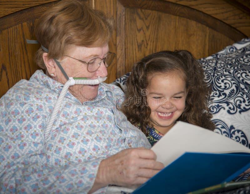 Η γυναίκα στο οξυγόνο διαβάζει στο μικρό κορίτσι στοκ φωτογραφία