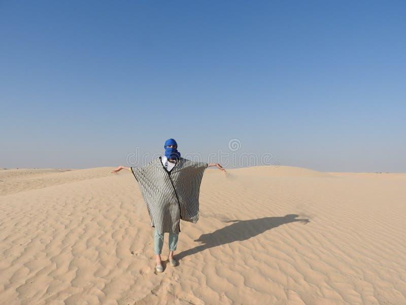 Η γυναίκα στο τουρμπάνι, πρόσωπο κάλυψε, στην έρημο Σαχάρας, Αφρική, σαφής ημέρα, μπλε ουρανός, κίτρινη άμμος στοκ εικόνα