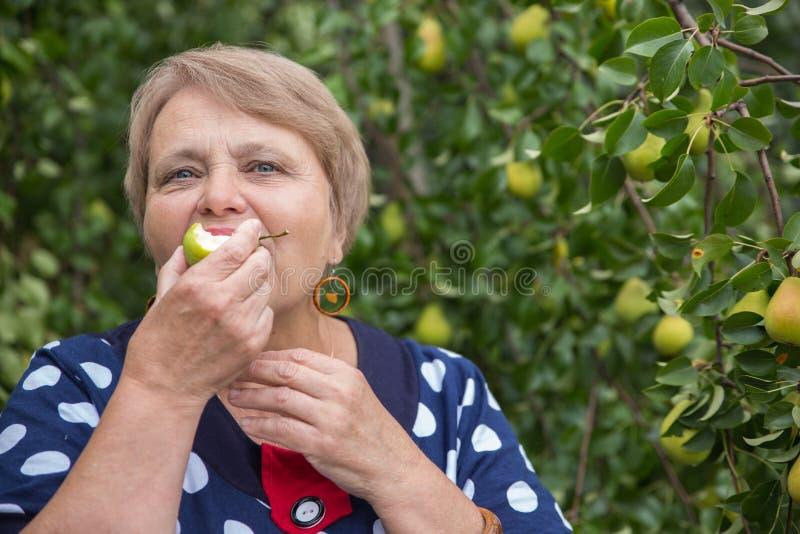 Η γυναίκα συνταξιούχων τρώει το αχλάδι κάτω από το δέντρο αχλαδιών στοκ φωτογραφία με δικαίωμα ελεύθερης χρήσης