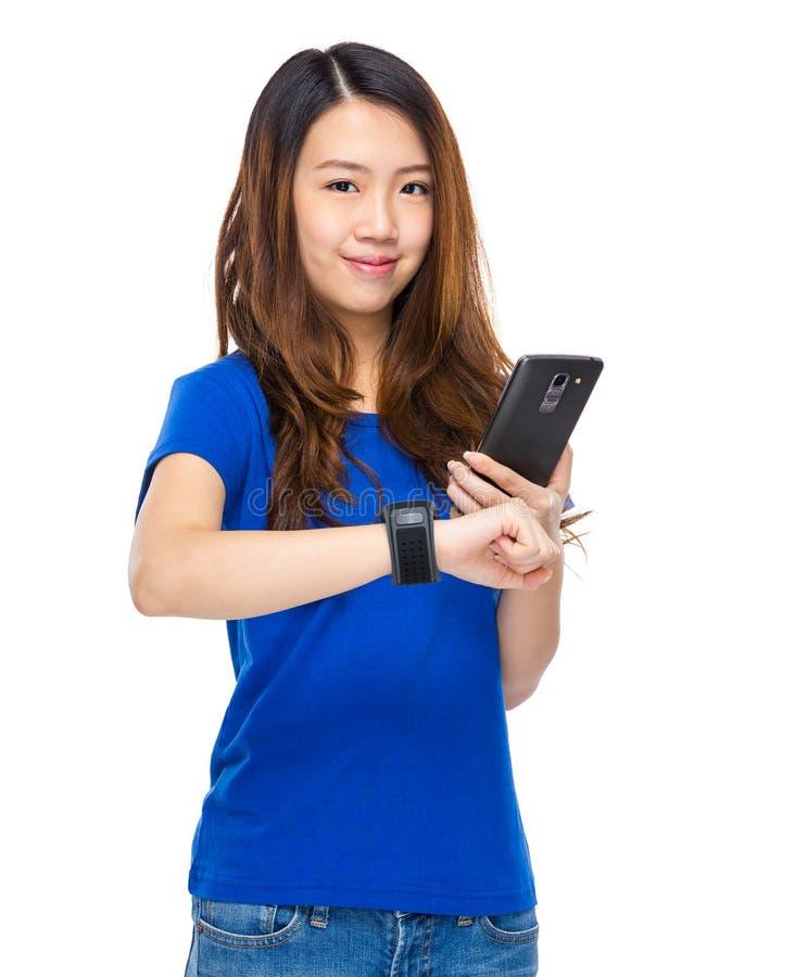 Η γυναίκα συνδέει τη φορετή συσκευή με το κινητό τηλέφωνο στοκ φωτογραφίες