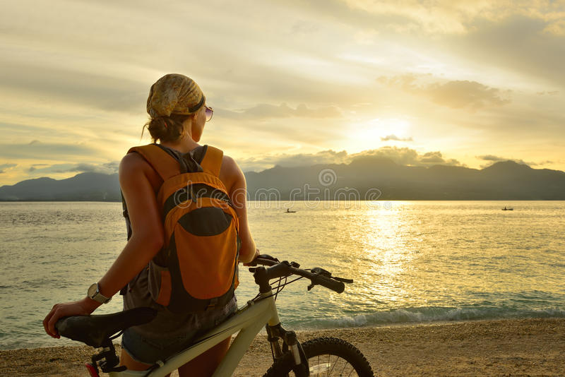 Η γυναίκα ταξιδεύει με ένα σακίδιο πλάτης στο ποδήλατό της στοκ εικόνες