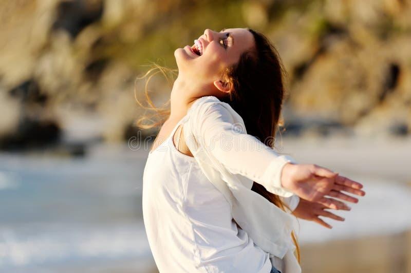 Η γυναίκα τεντώνει έξω τα όπλα της στη χαρά από τον ωκεανό στοκ εικόνες με δικαίωμα ελεύθερης χρήσης