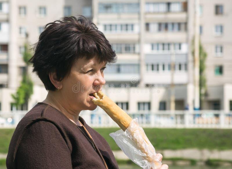 Η γυναίκα τρώει τη μακριά φραντζόλα στην οδό στοκ εικόνα