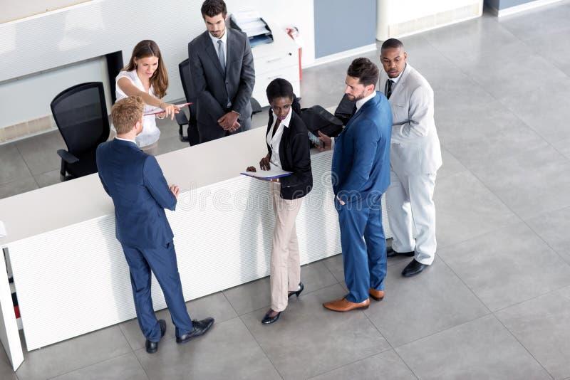 Η γυναίκα υποδοχής εξηγεί στον επιχειρηματία στοκ φωτογραφία