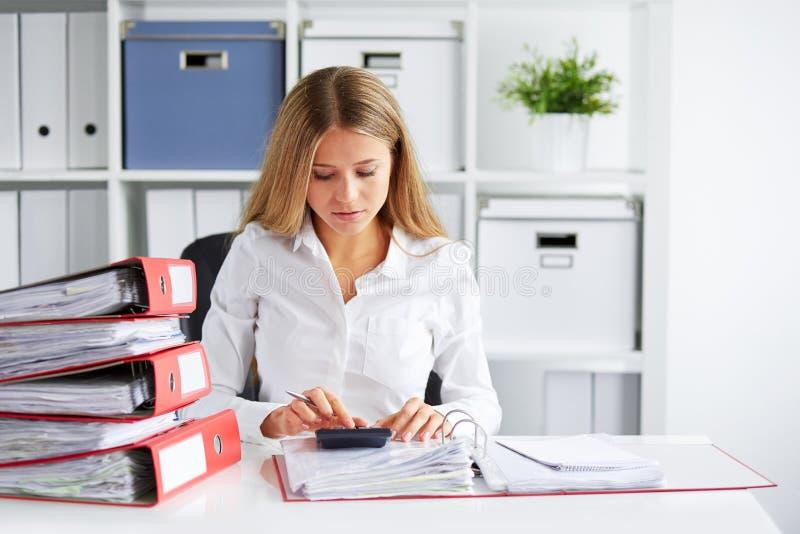 Η γυναίκα υπολογίζει το φόρο στοκ εικόνες