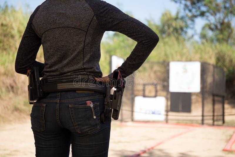 Η γυναίκα φέρνει το πυροβόλο όπλο στη ζώνη του στοκ εικόνες
