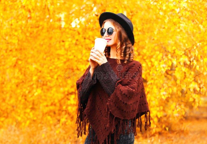 Η γυναίκα φθινοπώρου μόδας πίνει τον καφέ στο μαύρο στρογγυλό καπέλο, πλεκτό poncho στοκ εικόνες με δικαίωμα ελεύθερης χρήσης