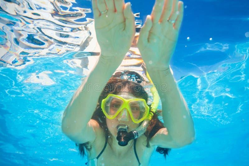 Η γυναίκα φορά την κολύμβηση μασκών κολύμβησης με αναπνευστήρα υποβρύχια στοκ εικόνες