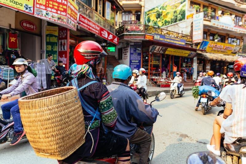 Η γυναίκα φυλών Hill φέρνει το καλάθι σε την πίσω και κάθεται στη πίσω θέση της μοτοσικλέτας στην περιοχή αγοράς το καλοκαίρι σε  στοκ εικόνες με δικαίωμα ελεύθερης χρήσης