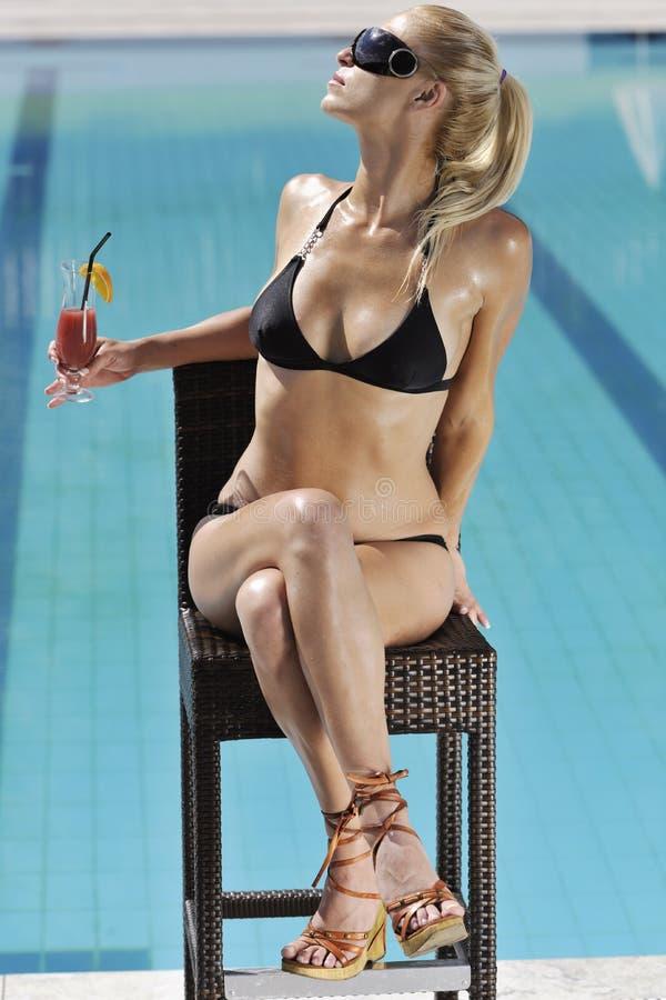 Η γυναίκα χαλαρώνει και πίνει coctail στην πισίνα στοκ φωτογραφία