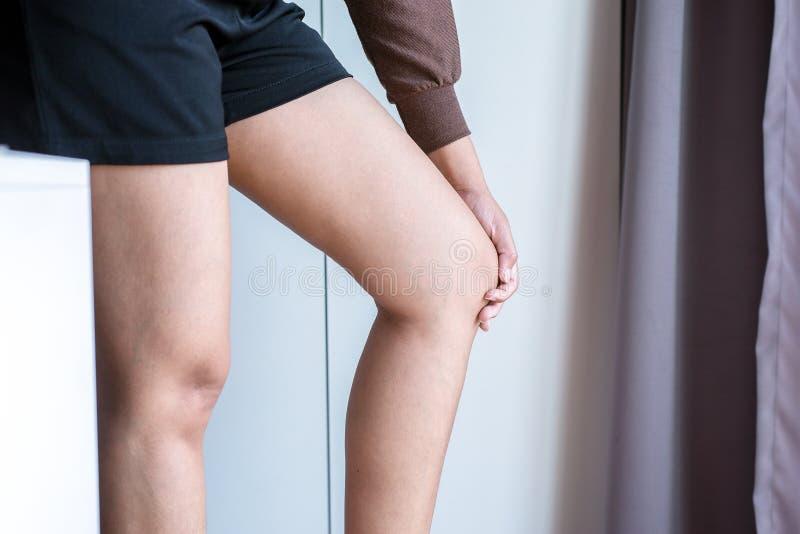 Η γυναίκα χεριών σχετικά με το πόδι της και την κατοχή ενός πόνου γονάτων, θηλυκό συναίσθημα εξάντλησε και επίπονος στοκ φωτογραφίες