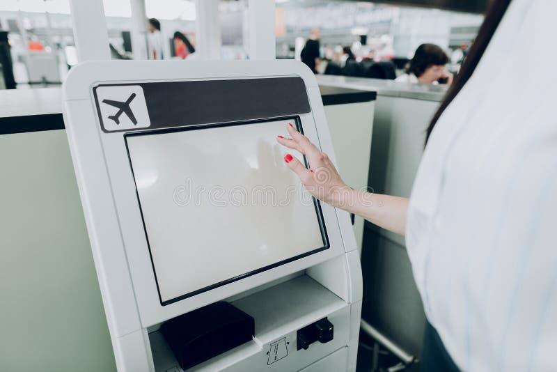 Η γυναίκα χρησιμοποιεί τη μηχανή του ATM στον αερολιμένα στοκ εικόνες