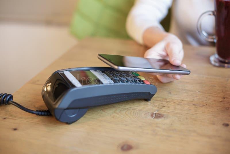Η γυναίκα χρησιμοποιεί το έξυπνο τηλέφωνο για να πληρώσει στοκ εικόνες με δικαίωμα ελεύθερης χρήσης