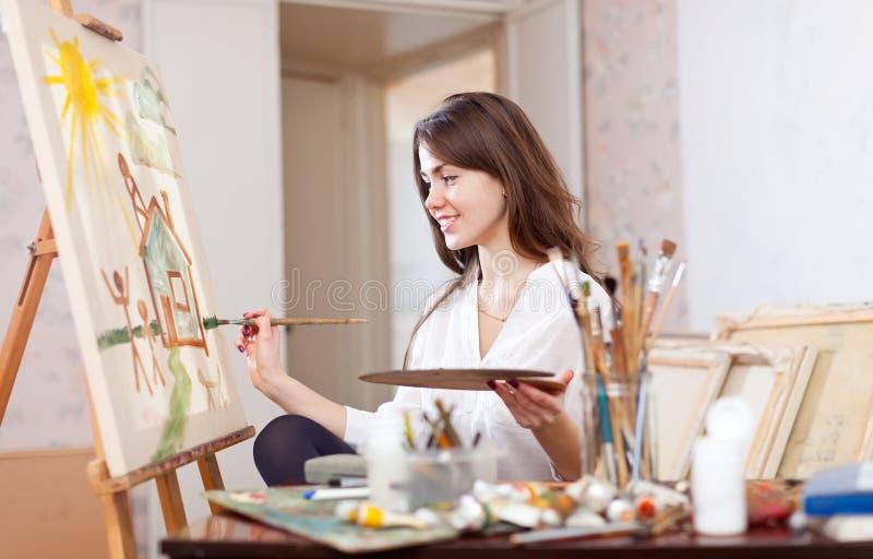 Η γυναίκα χρωματίζει το τοπίο στον καμβά στοκ εικόνες