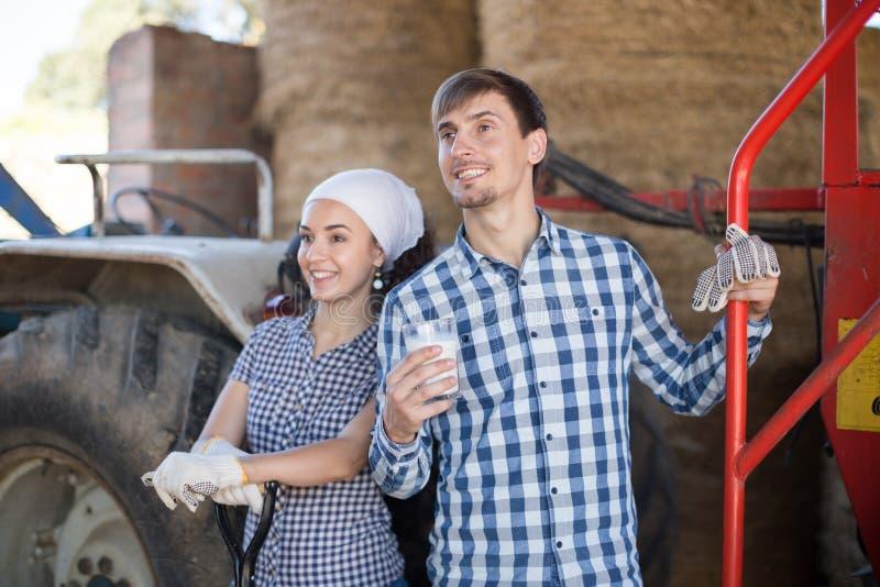 Η γυναίκα χώρας δίνει στο ποτήρι οδηγών τρακτέρ ανδρών του γάλακτος στο αγρόκτημα στοκ φωτογραφία