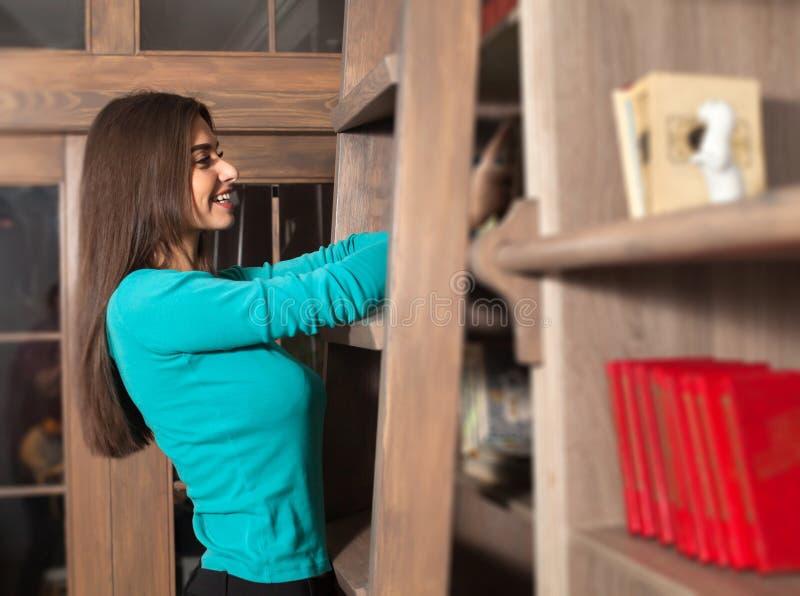 Η γυναίκα ψάχνει ένα βιβλίο στοκ εικόνες