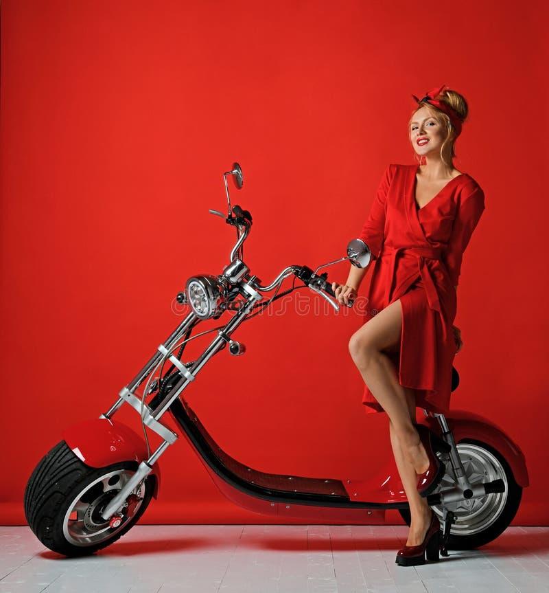 Η γυναίκα pinup ορίζει το νέο ηλεκτρικό μηχανικό δίκυκλο ποδηλάτων μοτοσικλετών αυτοκινήτων γύρου παρόν για το νέο έτος 2019 στοκ εικόνες με δικαίωμα ελεύθερης χρήσης