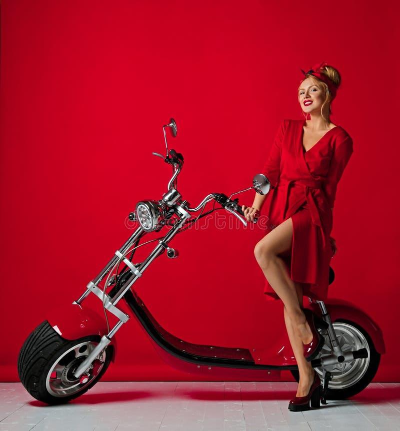 Η γυναίκα pinup ορίζει το νέο ηλεκτρικό μηχανικό δίκυκλο ποδηλάτων μοτοσικλετών αυτοκινήτων γύρου παρόν για το νέο έτος 2019 στοκ εικόνες