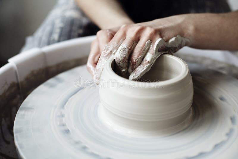 Η γυναίκα ` s δίνει κοντά επάνω, το δεσποτικό στούντιο των εργασιών κεραμικής με τον άργιλο σε μια ρόδα αγγειοπλαστών ` s στοκ εικόνα