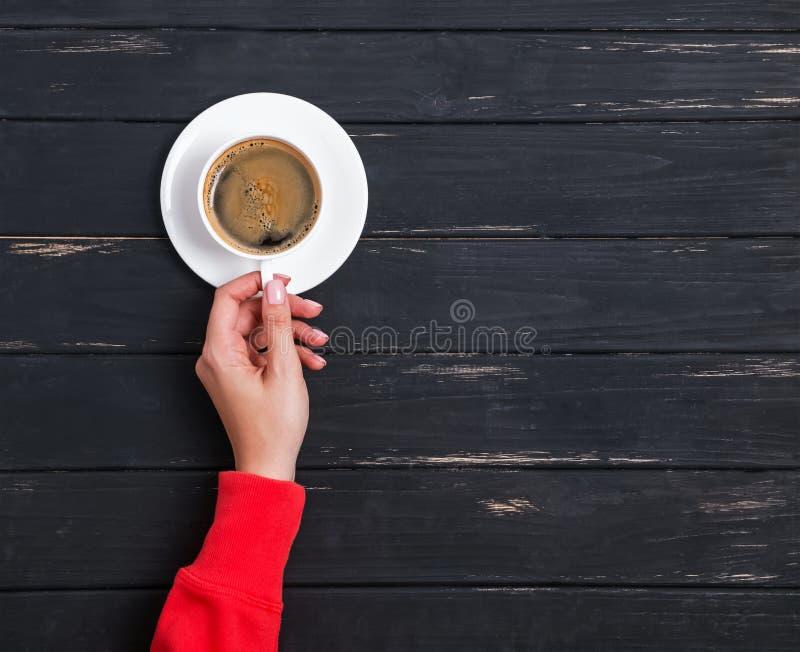 Η γυναίκα ` s παραδίδει τον κόκκινο ιματισμό κρατώντας ένα φλιτζάνι του καφέ στο μαύρο ξύλινο υπόβαθρο στοκ φωτογραφίες με δικαίωμα ελεύθερης χρήσης