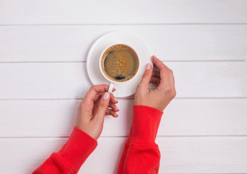 Η γυναίκα ` s παραδίδει τον κόκκινο ιματισμό κρατώντας ένα φλιτζάνι του καφέ στον άσπρο ξύλινο πίνακα στοκ εικόνα με δικαίωμα ελεύθερης χρήσης