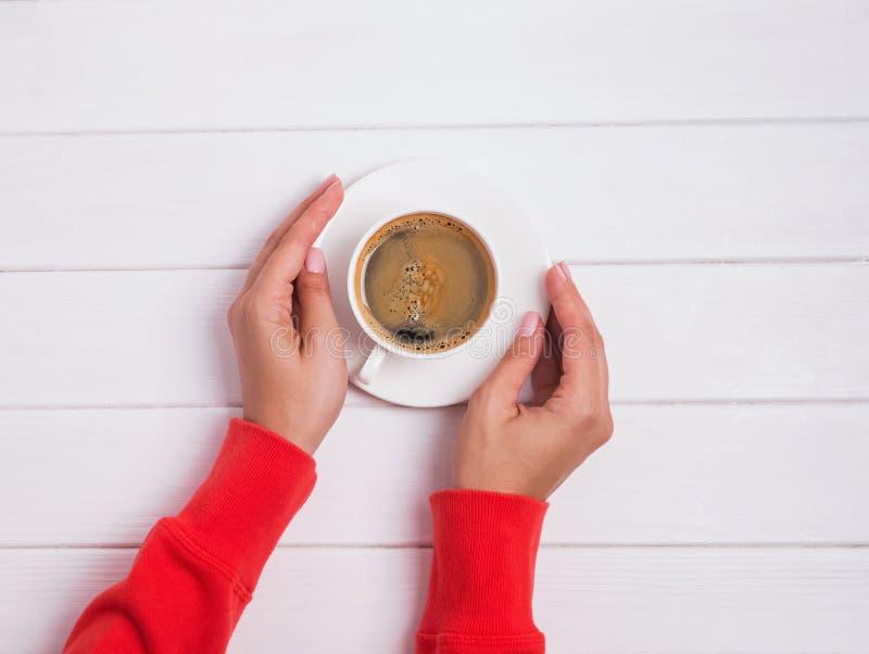 Η γυναίκα ` s παραδίδει το φωτεινό κόκκινο ιματισμό κρατώντας ένα φλιτζάνι του καφέ στοκ φωτογραφία