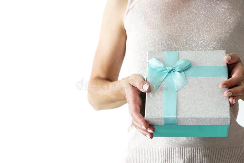 Η γυναίκα sparkly στο πουκάμισο κρατά το κιβώτιο δώρων με την κορδέλλα στα χέρια στοκ εικόνα με δικαίωμα ελεύθερης χρήσης