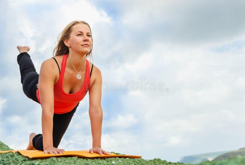 Η γυναίκα Yuong κάνει την εύκαμπτη άσκηση γιόγκας στοκ εικόνα