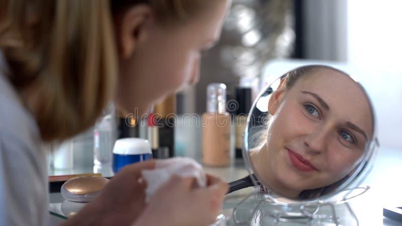 Η γυναικεία συνεδρίαση μπροστά από τον καθρέφτη και την εκμετάλλευση να καθαρίσει χεριών του προσώπου σκουπίζει στοκ φωτογραφίες με δικαίωμα ελεύθερης χρήσης