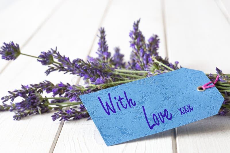 Η δέσμη lavender των λουλουδιών, με την αγάπη και τα φιλιά που γράφονται σε ένα δώρο κολλούν την ετικέτα στοκ φωτογραφίες