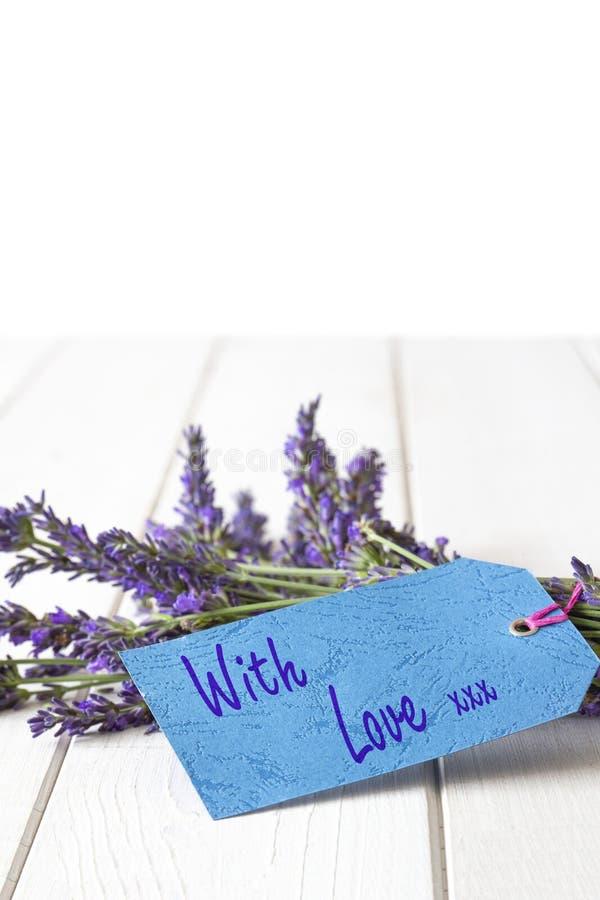 Η δέσμη lavender των λουλουδιών, με την αγάπη και τα φιλιά που γράφονται σε ένα δώρο κολλούν την ετικέτα στοκ φωτογραφία με δικαίωμα ελεύθερης χρήσης