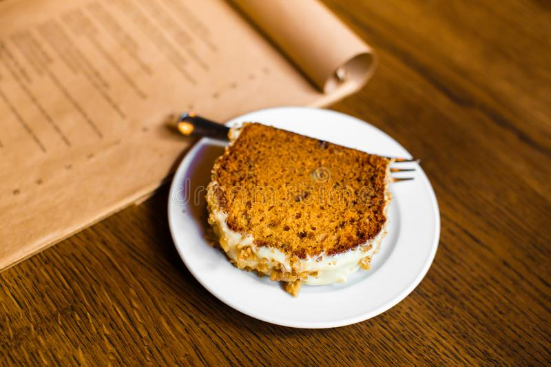 Η δευτερεύουσα φωτογραφία του εύγευστου κέικ σφουγγαριών που διακοσμείται με την άσπρα σοκολάτα και τα καρύδια Το επιτραπέζιο σύν στοκ εικόνες