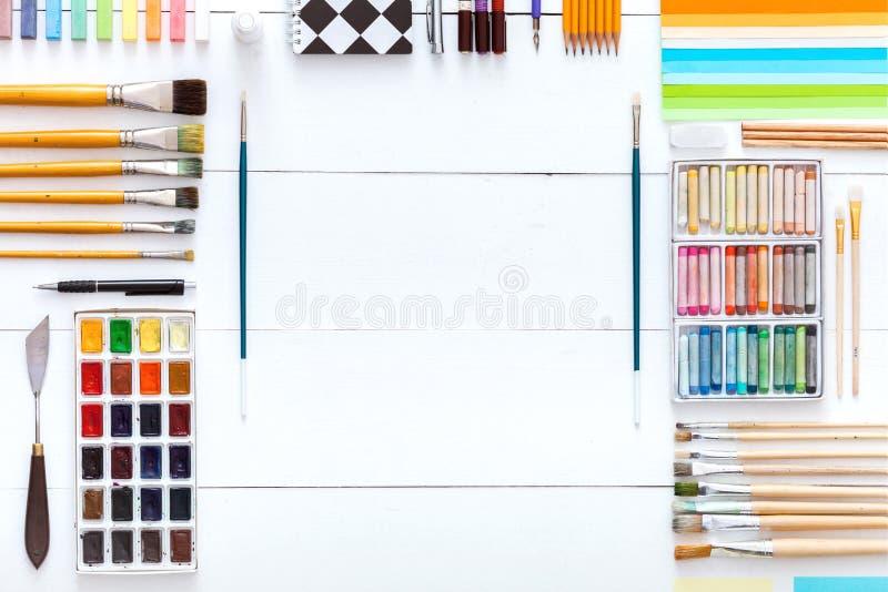 Η δημιουργική εργασία τέχνης παρέχει τα ζωηρόχρωμα εξαρτήματα που τίθενται στο άσπρο ξύλινο υπόβαθρο, μολύβια κραγιονιών watercol στοκ εικόνα