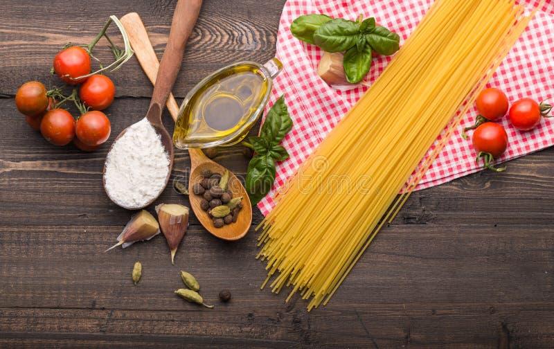 Η διαδικασία το υπόβαθρο τροφίμων για τα νόστιμα ιταλικά πιάτα με την ντομάτα Διάφορα μαγειρεύοντας συστατικά με τα μακαρόνια και στοκ φωτογραφία