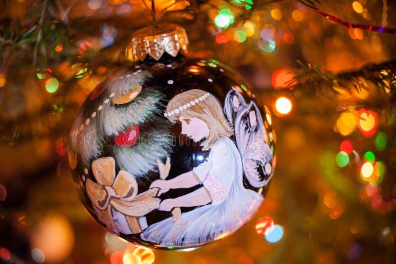 Η διακοσμητική νέα σφαίρα παιχνιδιών έτους με το χρωματισμένο άγγελο κρεμά στο χριστουγεννιάτικο δέντρο στοκ εικόνα