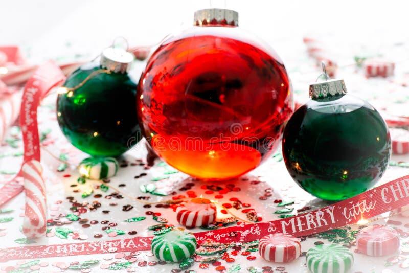 Η διακόσμηση με το κόκκινο ρευστό γέμισε τη σφαίρα διακοσμήσεων Χριστουγέννων και δύο πράσινες γεμισμένες σφαίρες διακοσμήσεων πο στοκ εικόνες