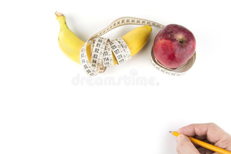 Η διατροφή, η υγιής κατανάλωση, τα τρόφιμα και ζυγίζουν την έννοια απώλειας - κλείστε επάνω του μήλου μπανανών και μέτρηση της τα στοκ φωτογραφίες με δικαίωμα ελεύθερης χρήσης