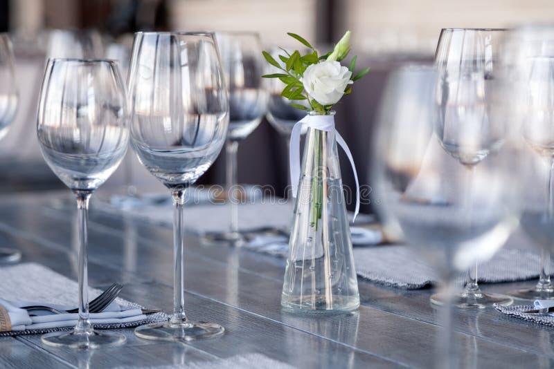 Η διαφανής σύγχρονη ρύθμιση, βάζο γυαλιού με την ανθοδέσμη ανθίζει στον πίνακα στο εστιατόριο Στάση γυαλιών κρασιού και νερού στο στοκ φωτογραφίες