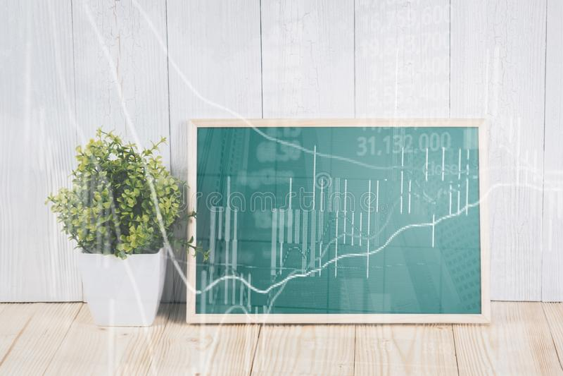 Η διπλή έκθεση του κενού πράσινου chalkborad και λίγο δέντρο στον ξύλινο πίνακα με το διάγραμμα οθόνης χρηματιστηρίου επιβιβάζοντ στοκ εικόνα με δικαίωμα ελεύθερης χρήσης